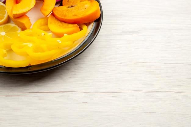Vista da metade inferior de legumes e frutas picados, pimentões de abóbora, caqui na placa preta na superfície branca, espaço livre