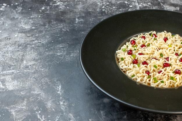 Vista da metade inferior de macarrão ramen com sabor de romã no espaço livre da mesa escura