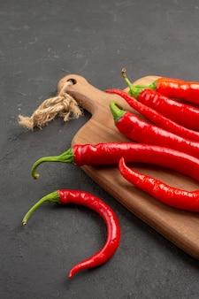 Vista da metade inferior de pimentas vermelhas em uma tábua de cortar em fundo preto