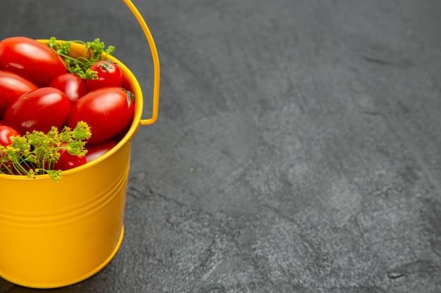 Vista da metade inferior do balde de tomates cereja e flores de endro à esquerda do fundo escuro