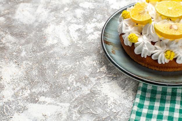 Vista da metade inferior do bolo com creme de confeiteiro branco e rodelas de limão em prato redondo em mesa quadriculada verde e branca