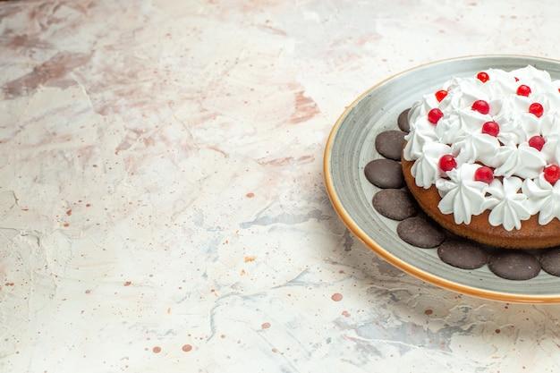 Vista da metade inferior do bolo com creme de confeiteiro e chocolate na superfície bege