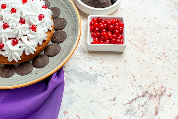 Vista da metade inferior do bolo com creme de confeiteiro em prato oval xale roxo de chocolate e frutas em tigelas na mesa branca