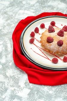 Vista da metade inferior do bolo de frutas vermelhas em um prato oval branco xale vermelho na superfície cinza