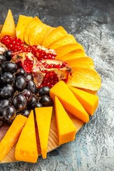 Vista da metade inferior do queijo fatiando uvas e romã em uma tábua oval no escuro