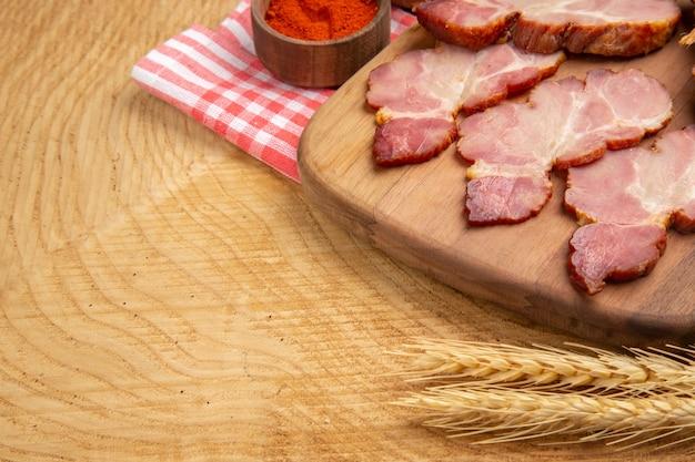 Vista da metade inferior fatias de becon na mesa de servir pimenta vermelha em uma tigela pequena espiga de trigo na mesa de madeira