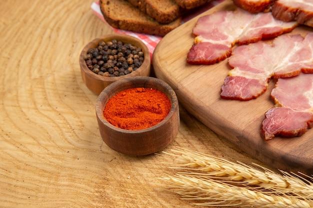Vista da metade inferior fatias de becon na tábua de cortar pimenta vermelha e preta em uma tigela pequena na mesa de madeira