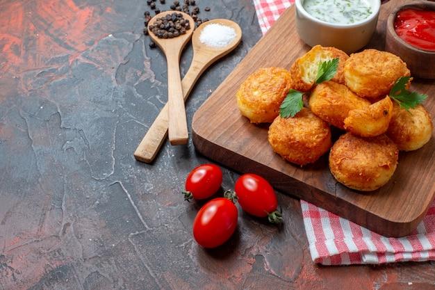 Vista da metade inferior nuggets de frango na tábua de madeira com molhos, tomate cereja, colheres de pau, pimenta preta na mesa escura, espaço livre