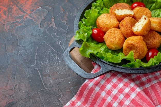 Vista da metade inferior nuggets de frango, tomate cereja e alface em uma panela com fundo escuro