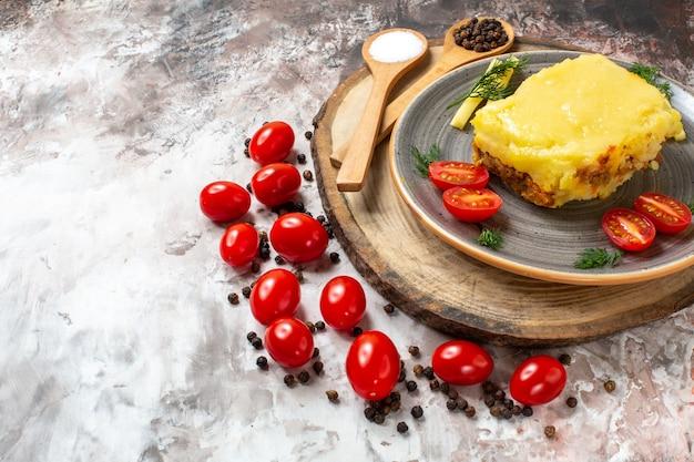 Vista da metade inferior, pão de queijo, tomate no prato, colheres de madeira no prato rústico servindo tomate cereja no lugar da cópia da mesa