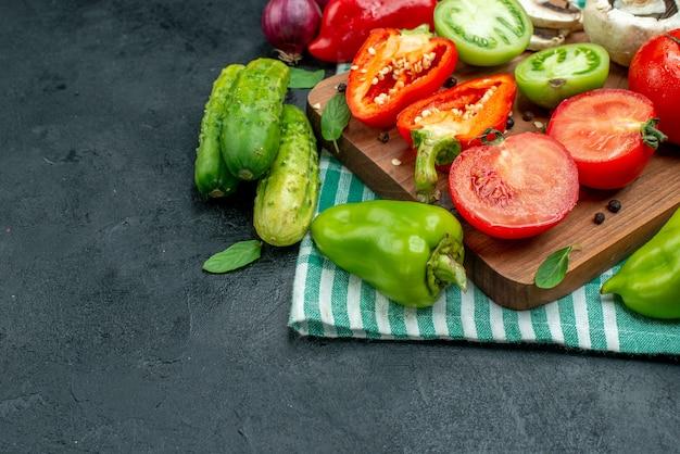 Vista da metade inferior vegetais cogumelos tomates pimentões na tábua de corte pepinos cebola vermelha na mesa preta cópia local