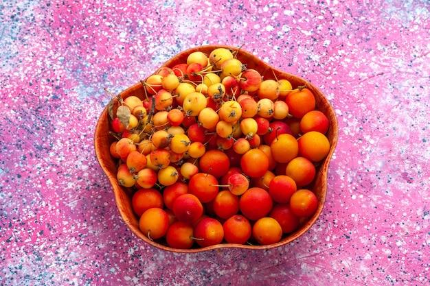 Vista da metade superior cerejas doces frescas com ameixas dentro do prato na mesa rosa.