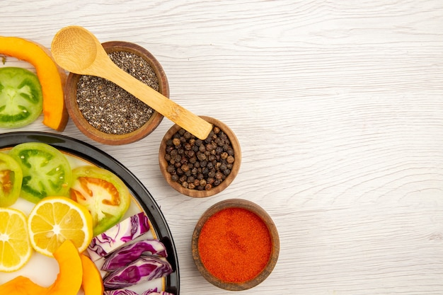 Vista da metade superior corte legumes e frutas abóbora pimentões caqui repolho roxo na placa preta especiarias em pequenas tigelas colher de madeira no espaço da cópia da mesa de madeira
