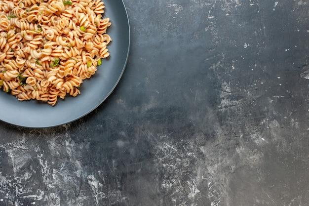 Vista da metade superior da massa rotini em prato redondo na superfície escura foto de comida do espaço livre