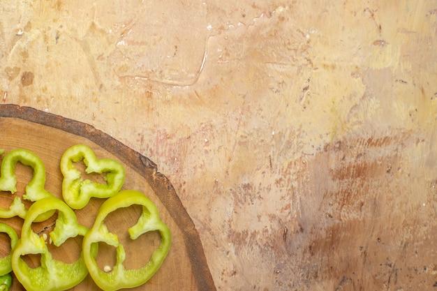 Vista da metade superior de pimentões cortados em pedaços em uma placa redonda de madeira com fundo âmbar