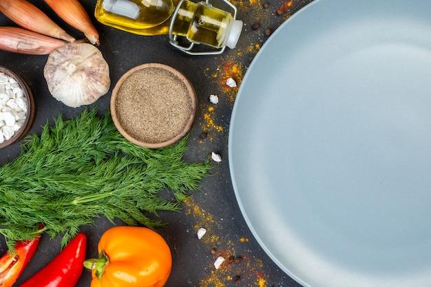Vista da metade superior de um prato redondo cinza de legumes frescos e outros alimentos no escuro