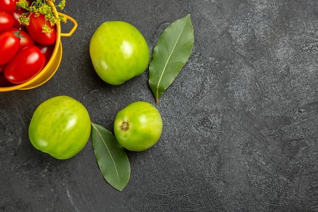 Vista da metade superior do balde amarelo cheio de tomates cereja e flores de endro, folhas de louro e tomates verdes em solo escuro