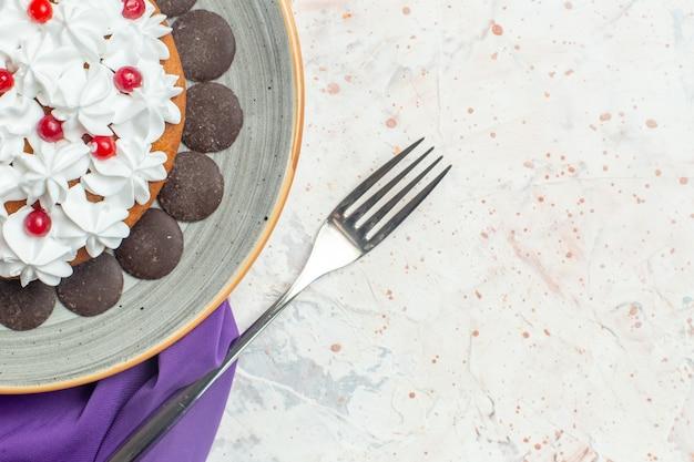 Vista da metade superior do bolo com creme de confeitaria no prato xale roxo