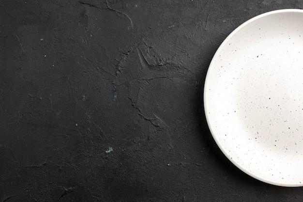 Vista da metade superior do prato de salada branca no espaço livre da mesa escura