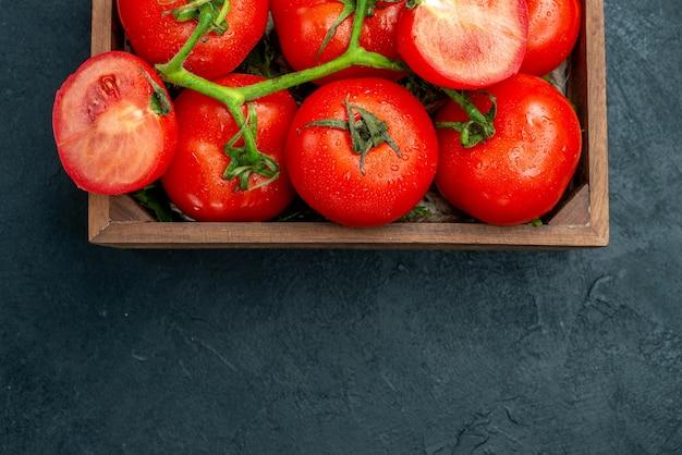 Vista da metade superior tomates vermelhos cortados em uma caixa de madeira no espaço livre da mesa preta