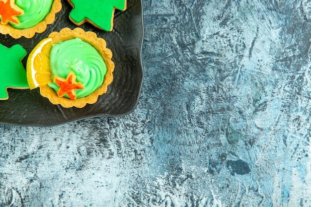 Vista da metade superior tortinhas com creme verde, biscoitos da árvore de natal na placa preta na superfície cinza com espaço de cópia