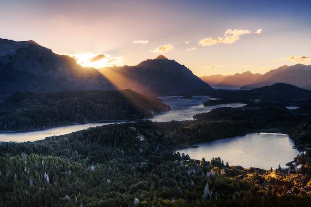 Vista da montanha de um raio de luz do sol iluminando um lago