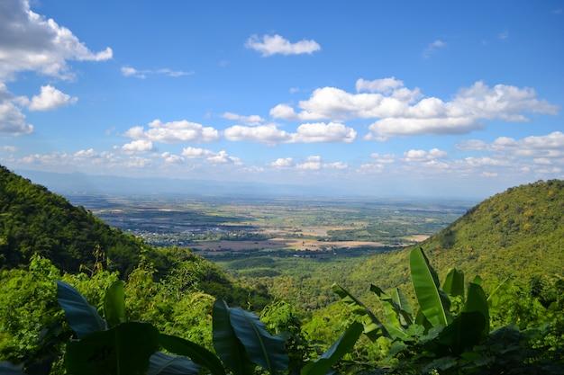 Vista da montanha e o céu é azul com nuvens brancas.