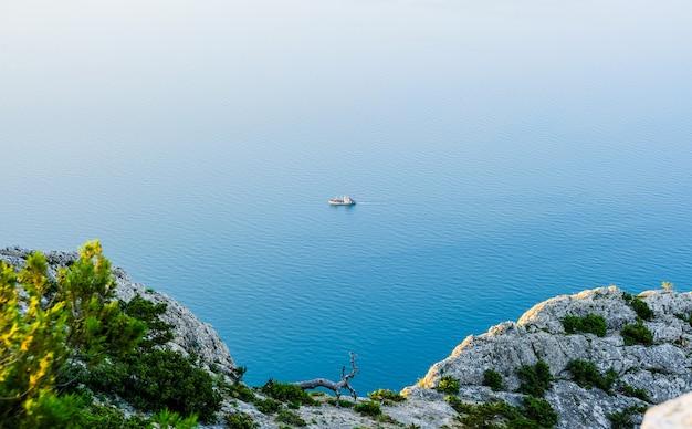 Vista da montanha para o mar e um navio solitário