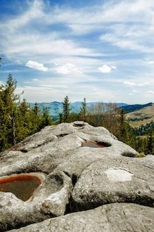 Vista da montanha pedra escrita na paisagem montanhosa dos cárpatos. montanhas dos cárpatos vista superior paisagem cume verão temporada tempo dramático com fundo de céu azul nublado.