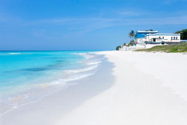 Vista da orla de uma praia paradisíaca em varadero com águas cristalinas, areia branca e céu azul.
