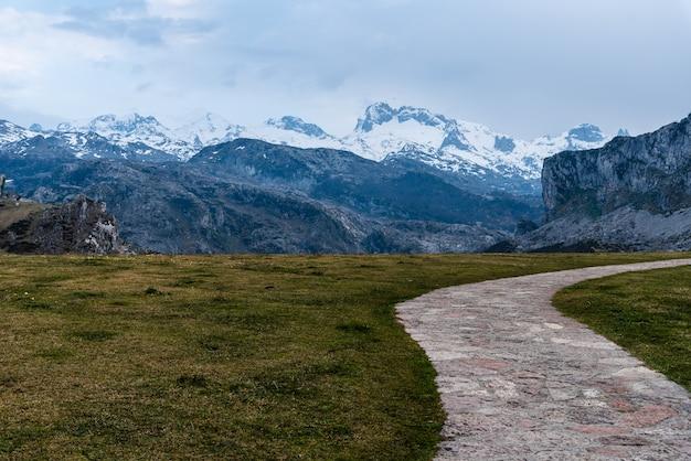 Vista da paisagem das montanhas rochosas cobertas de neve com grama e uma estrada em primeiro plano