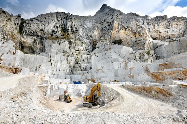 Vista da paisagem de uma pedreira de mármore a céu aberto em carrara, toscana, itália, mostrando o equipamento pesado e a face rochosa