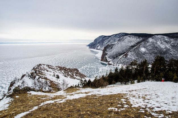 Vista da paisagem do inverno na sibéria com o lago baikal congelado à distância. inverno na rússia