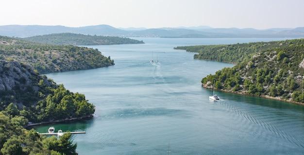 Vista da paisagem do rio krka, na croácia, cercado por árvores e montanhas
