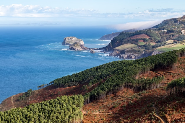 Vista da paisagem marinha de uma praia e falésias rochosas com o mar desaparecendo no horizonte, céu azul com nuvens brancas, vizcaya, país basco. espanha