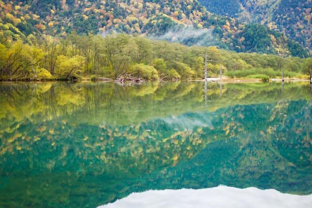 Vista da paisagem natural da floresta de cor vermelho-laranja outono com a reflexão sobre a superfície do lago