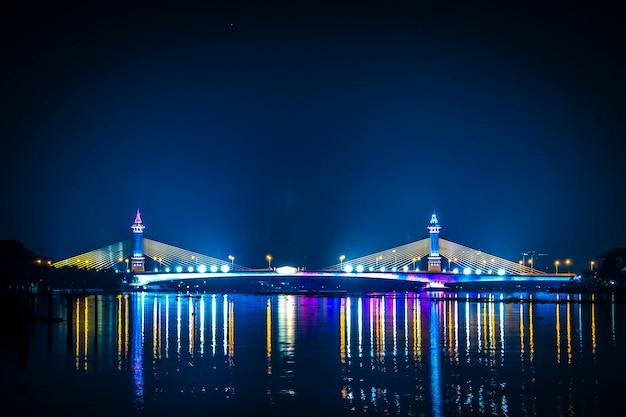 Vista da paisagem noturna da cidade na tailândia, com belos reflexos de arranha-céus e pontes à beira do rio no crepúsculo. vista panorâmica da ponte sobre o rio chao phraya