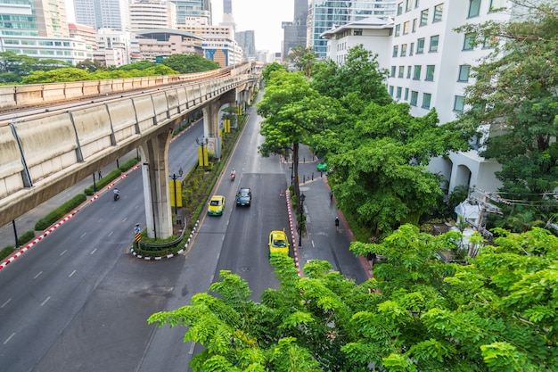 Vista da paisagem urbana de alguns carros na estrada ao longo da via férrea com muitos árvore
