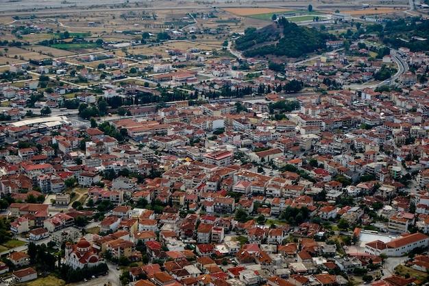 Vista da paisagem urbana de antigos edifícios de telhado vermelho em kalambaka de rocha de mosteiros de meteora