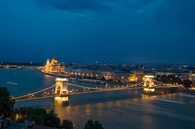 Vista da paisagem urbana do rio danúbio à noite com grande ponte luminosa em budapeste.