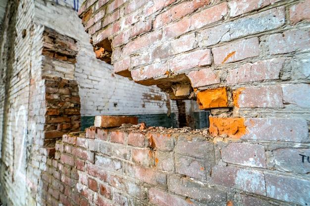 Vista da parede de ruptura na antiga fábrica. dano abandonado velho da fábrica da ruína que constrói para dentro