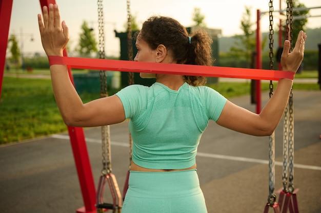 Vista da parte de trás de uma jovem esportiva afro-americana, mestiça, hispânica, se exercitando, esticando os braços com elástico de borracha e fazendo exercícios ao ar livre em um campo esportivo ao nascer do sol