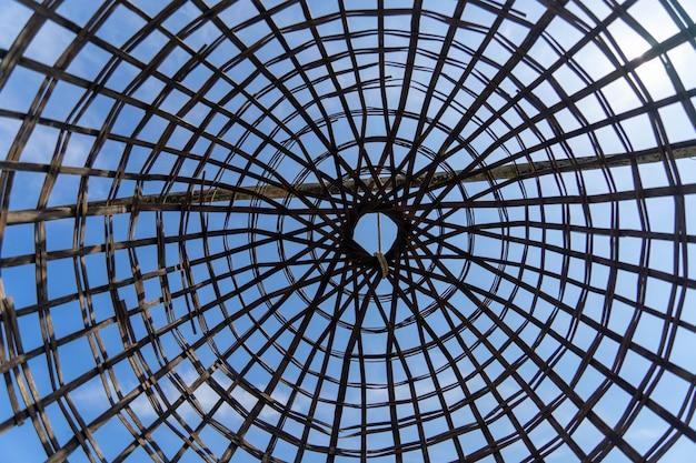 Vista da parte inferior da gaiola tradicional da pesca feita do bambu com o céu azul no fundo.