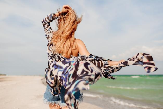 Vista da parte traseira da mulher graciosa despreocupada, com cabelos ruivos incríveis correndo ao longo da praia