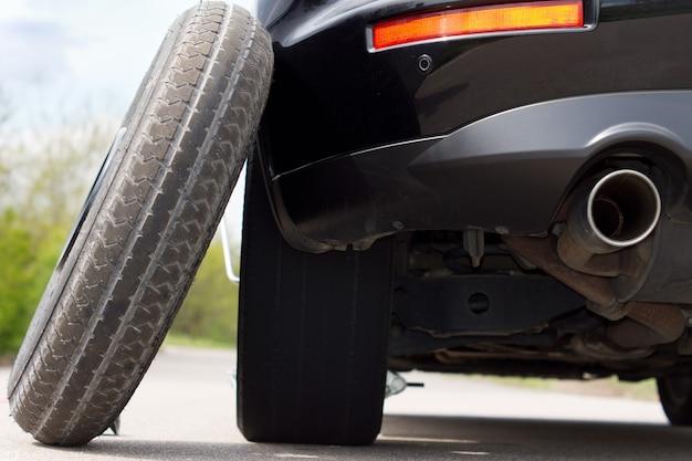 Vista da parte traseira do veículo mostrando o tubo de escape de um pneu sobressalente equilibrado contra um carro