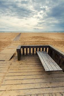Vista da passagem de madeira em uma linha costeira vazia longa da praia.