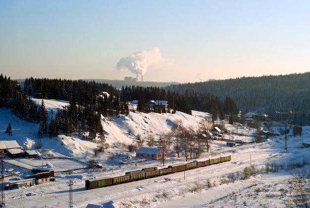 Vista da pequena estação ferroviária no vale de inverno com vagões de carga em pé