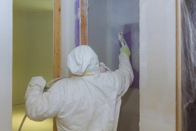 Vista da pintura parede de pintura do homem. usando a pistola do lado close-up vista