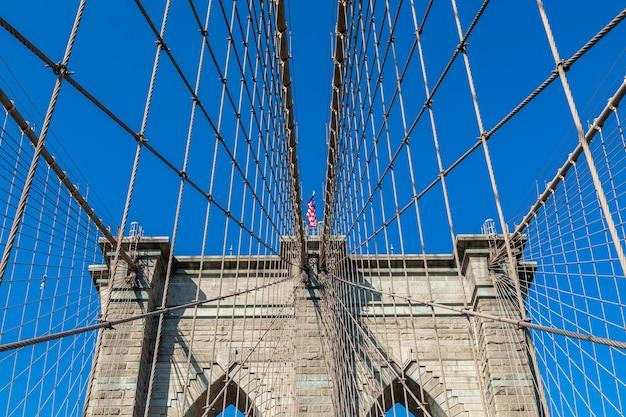 Vista da ponte de brooklyn com estais diagonais e cabos suspensores verticais. no centro da foto está a bandeira americana tremulando ao vento.
