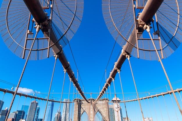 Vista da ponte de brooklyn com estais diagonais e cabos suspensores verticais.
